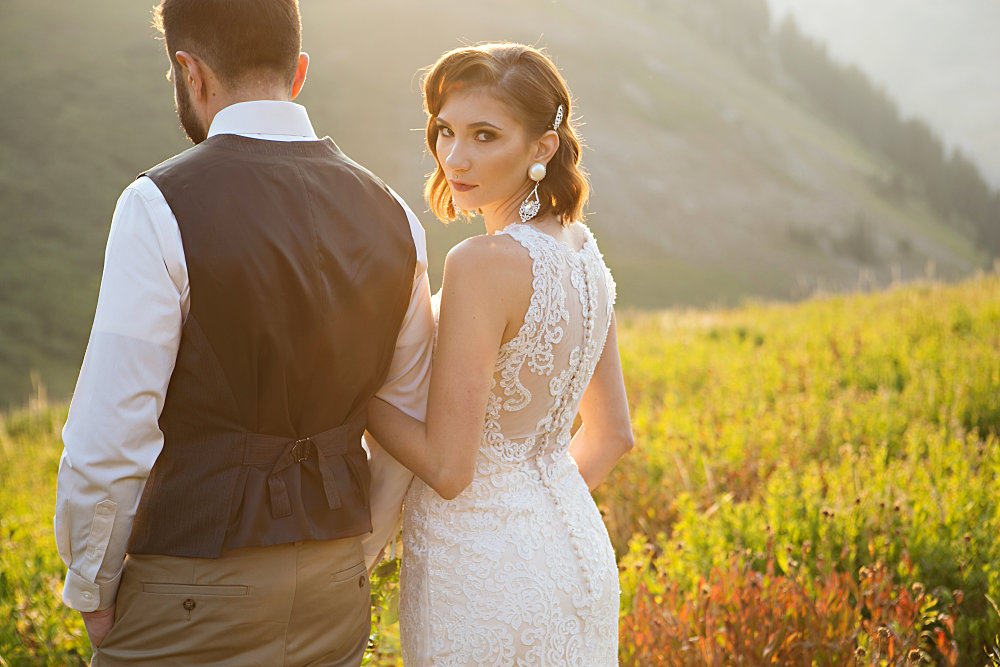 bride and groom in a field with utah mountains